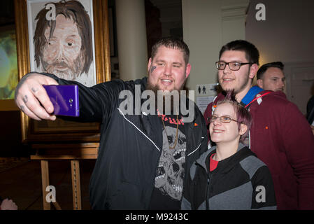 Brit award-winning singer-songwriter Rag 'n ' Bone Man (Rory Graham) takes a selfie with two young musicians at St Paul's, a venue in Worthing, West Sussex, England. Rag 'n' Bone Man was attending an event at the venue aimed at bringing together young musicians, venues and producers in the town. - Stock Photo