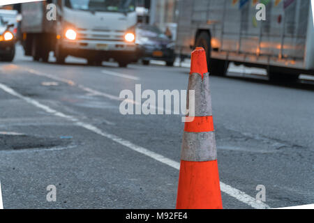 Road cone on side of busy city street to caution drivers around dangerous conditions - Stock Photo