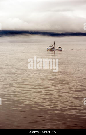 A commerical fishing boat onr man navigating heads out to see early morning in the fog - Stock Photo