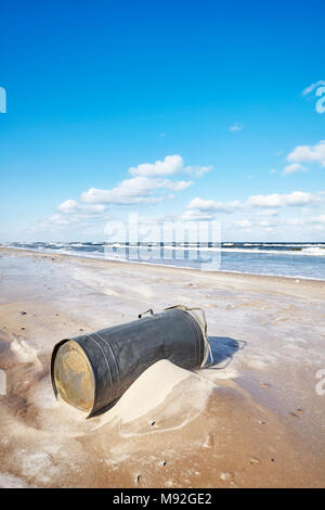 Old trash can on a beach, environmental pollution concept. - Stock Photo