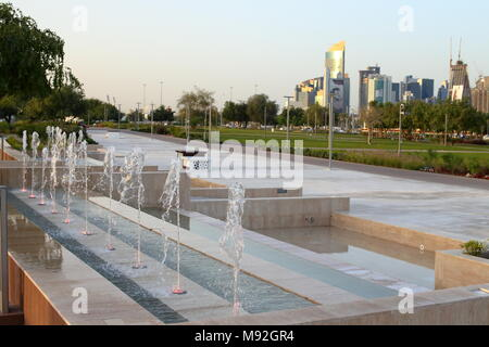 BIDDA PARK, Doha, Qatar - March 21, 2018: View of fountains in the newly opened Bidda Park in the centre of Qatar's capital, with distant city skyine. - Stock Photo