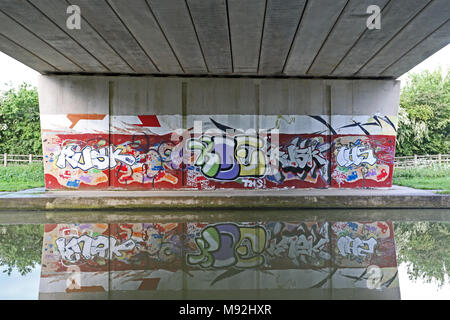 Graffiti beneath a road bridge is reflected in the calm water of the Grand Union Canal, Leighton Buzzard, Bedfordshire, UK. - Stock Photo