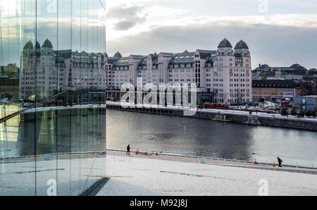 Oslo, Norway, March 16, 2018: Havnelageret, the old commercial building in Langkaia 1, reflected in the windows of the Oslo Opera House in Bjorvika. - Stock Photo