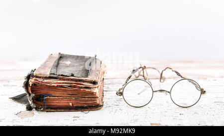 93fe2e86a2f Very old and worn book with antique round eyeglasses. Isolated on ...