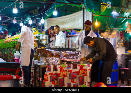 Chefs cooking at a food stall at the Djemaa el-Fna market in the Medina of Marrakesh, Morocco - Stock Photo