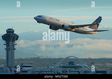 United Airlines Boeing 737-900 Jet Airliner Taking Off From Los Angeles International Airport, LAX. The Theme Building And Control Tower Behind. - Stock Photo