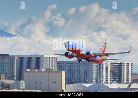 Southwest Airlines Boeing 737 Airliner Taking Off From Los Angeles International Airport, LAX, Clouds And Snow Covered San Gabriel Mountains Behind. - Stock Photo