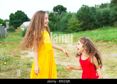 Two beautiful little girls playing and smiling at sunny summer day outdoors. Happy childhood concept - Stock Photo