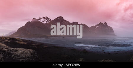 Vestrahorn Mountain in Iceland at sunset with black sand and a frozen lake in the foreground - Stock Photo