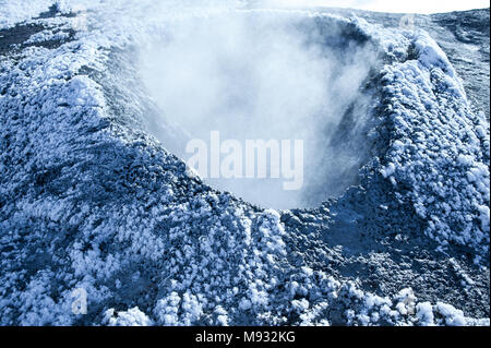 Steaming solfataras at Namafjall geothermal fields, Myvatn, Iceland. Close up of crater covered in ice crystals - Stock Photo