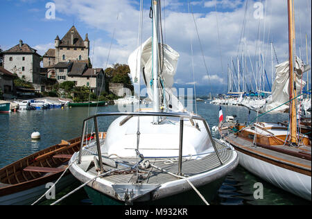 Sailing boats moored with their sails furled in a pretty lakeside harbour with castle in background on Lake Geneva.  Yvoire, France - Stock Photo