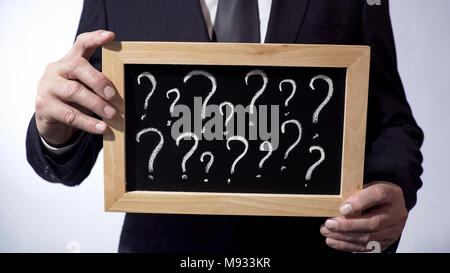 Question marks written on blackboard, male wearing classic suit holding a sign - Stock Photo