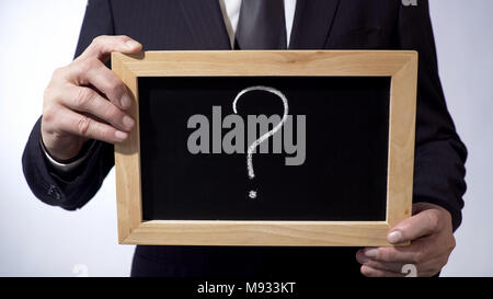 Question mark written on blackboard, business person holding a sign in hands - Stock Photo