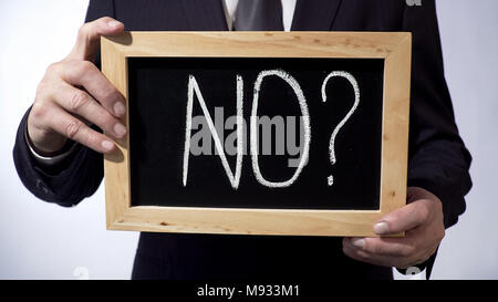 No with question mark written on blackboard, businessman holding sign, concept - Stock Photo
