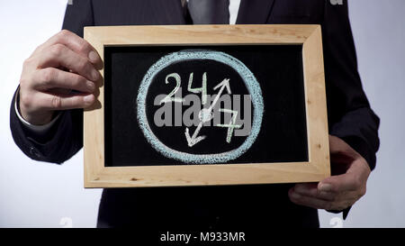 24 to 7 drawing on blackboard, businessman holding sign, business time concept - Stock Photo