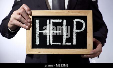 Help written on blackboard, man wearing black suit holding sign, consultation - Stock Photo