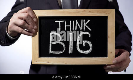 Think big written on blackboard, male in suit holding sign, motivational concept - Stock Photo