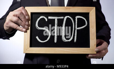 Stop written on blackboard, business person holding sign, motivation, honesty - Stock Photo