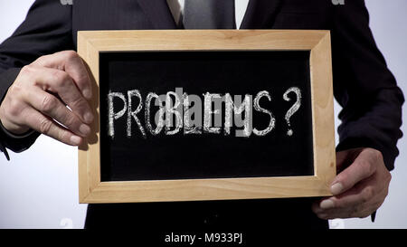 Problems with question mark written on blackboard, businessman holding sign - Stock Photo