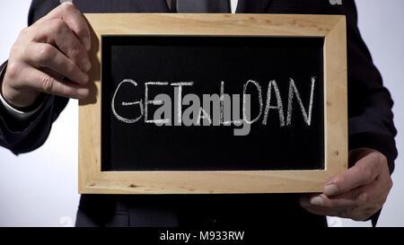 Get a loan written on blackboard, businessman holding sign, business concept - Stock Photo