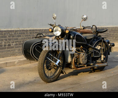 Old style motorbike and sidecar parked in a Hutong (residential lane) in Beijing, China - Stock Photo