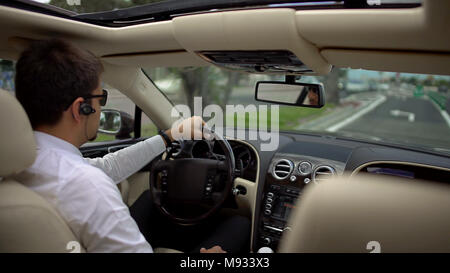Successful businessman driving expensive car to work, transportation service - Stock Photo