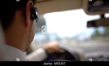 Busy rich man driving car to work, urban traffic, transportation service - Stock Photo
