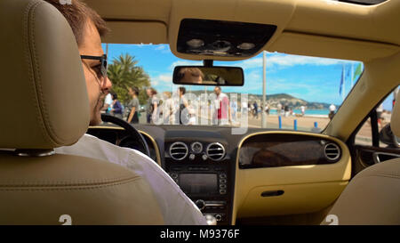 Rich man in sunglasses waiting for green light while sitting in expensive car - Stock Photo