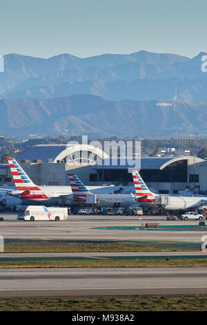 Tail Fins Of Parked American Airlines Aircraft At LAX, Los Angeles International Airport With The Hollywood Sign And The San Gabriel Mountains Behind. - Stock Photo