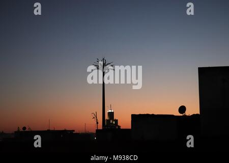 Mobile Phone Communication Mast Disguised as a Palm Tree, and a Mosque Silhouetted Against a Dramatic Sunset in Morocco - Stock Photo