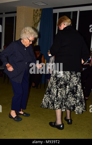 Senior women dancing with younger woman - Stock Photo