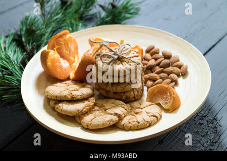 Almond cookies on a wooden plate with tangerines - Stock Photo