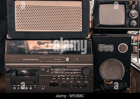Old vintage audio system with radio, cassette tape recorder, record player, TV set, acoustic speakers - Stock Photo