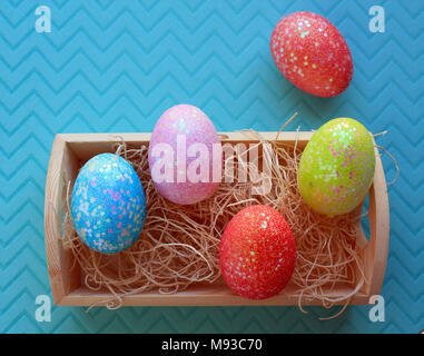five colorful Easter Eggs in a wooden box with nesting material inside on a pastel blue background - Stock Photo