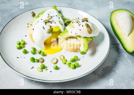 Delicious Poached Egg with Bread and Sliced Avocado on concrete background. - Stock Photo