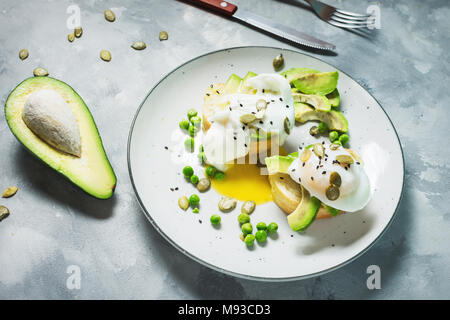 Delicious Poached Egg with Bread and Sliced Avocado on concrete background. Close-up - Stock Photo