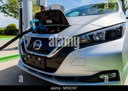 Pearland, Texas - March 21, 2018: New 2018 Nissan Leaf electric car plugged in to charge battery at the EVgo charging station - Stock Photo