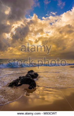 Evening clouds and gentle Pacific ocean surf at Kamaole Beach Park 11 at Kihei on the island of Maui in the state of Hawaii USA - Stock Photo