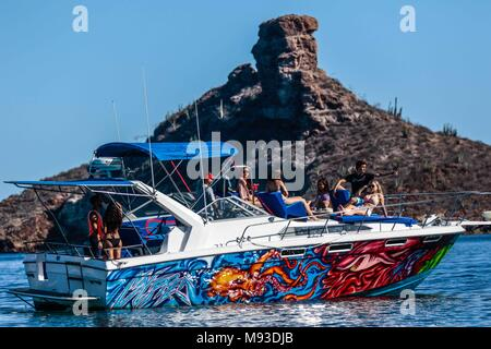 Teenage vacationers enjoy a sunny day, ride a yacht through the bay and beach of San Carlos, in the Gulf of Californai of the state of Sonora Mexico. - Stock Photo