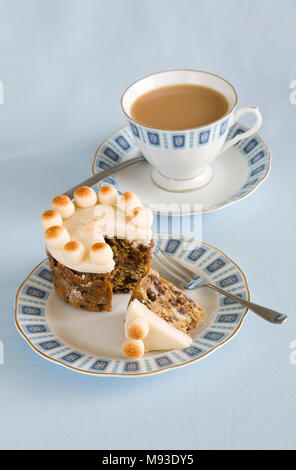 Homebaked miniature Simnel cake and a cup of tea. - Stock Photo