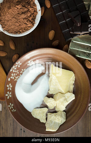 Preparation of dark chocolate bars made from scratch using cacao butter, sugar, cocoa powder and almonds - Stock Photo