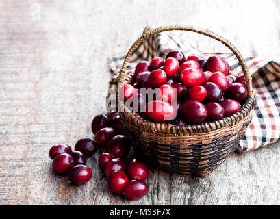 Fresh  cranberries in small wicker basket on wooden table - Stock Photo