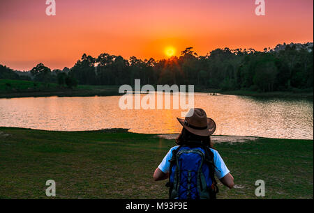 Woman tourist with hat and backpack standing with relax mood and watching sunset behind the pond and evergreen forest. Alone young woman - Stock Photo