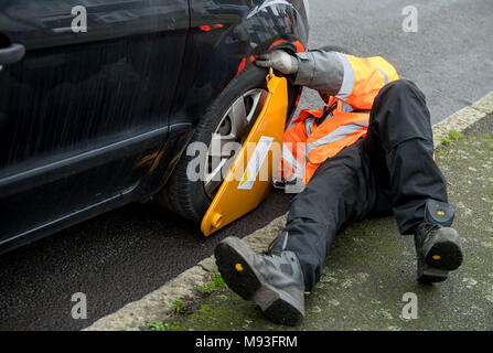 Wheel clamping of untaxed vehicles is becoming more common with the paper tax disc display being abolished and car tax needing to be paid online. - Stock Photo