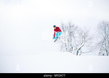 Photo of snowboarder man jumping on snowy hill - Stock Photo