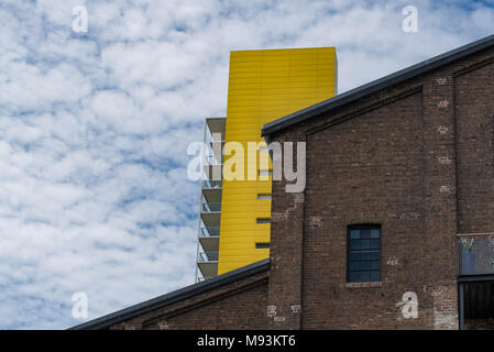 An old brick built warehouse in Pyrmont NSW with a brightly coloured modern apartment  in the background. - Stock Photo