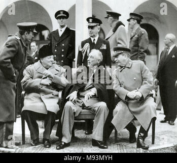 YALTA CONFERENCE February 1945. Seated from left: Winston Churchill, Franklin D. Roosevelt, Joseph Stalin. Fleet Admiral Ernest King  is standing behind Roosevelt. - Stock Photo