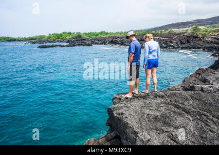 A man and woman stand atop a cliff above the ocean near Kona, Hawaii, The Big Island, USA.