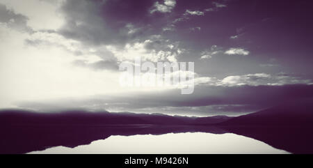 Scenic view of lake by trees and mountain against cloudy sky - Stock Photo