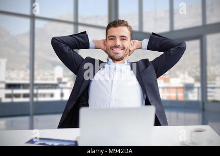 Composite image of portrait of smiling businessman with hands behind head sitting against white back - Stock Photo
